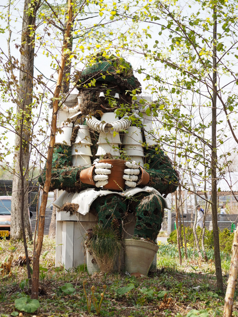 A Girl made of pots sitting in the yard of Ikoro no mori