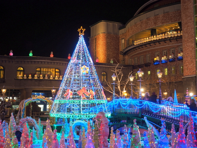 Big illuminated tree and small illuminated poles which are snowshed roses