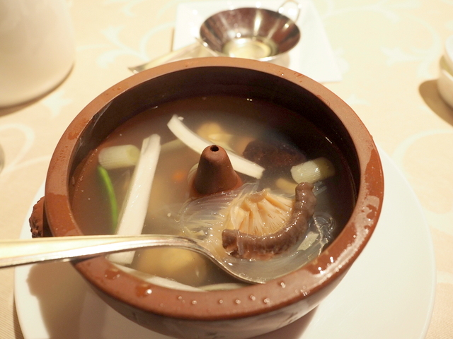 Chicken soup steamed in a crock with ginger oil