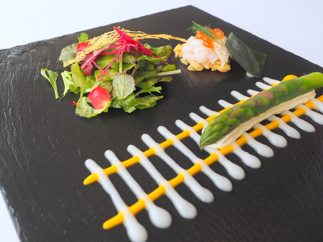 "Green asparagus and sea foods in the style of ""H5 Hayabusa"" with salmon roe and salad"